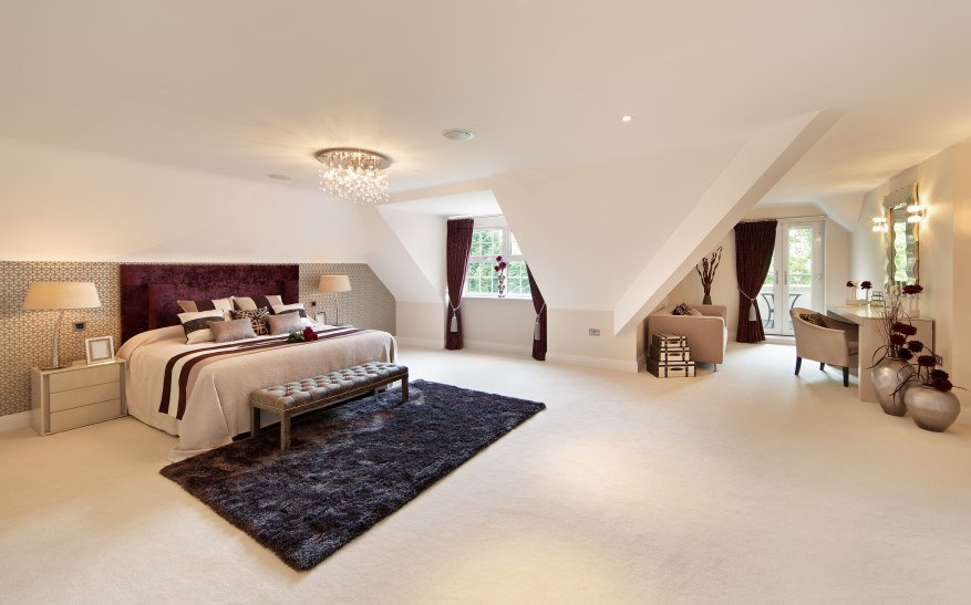 Large primary bedroom featuring white carpet flooring topped by an area rug. The bed is lighted by a luxurious chandelier. There's a sitting area and a powder desk as well.