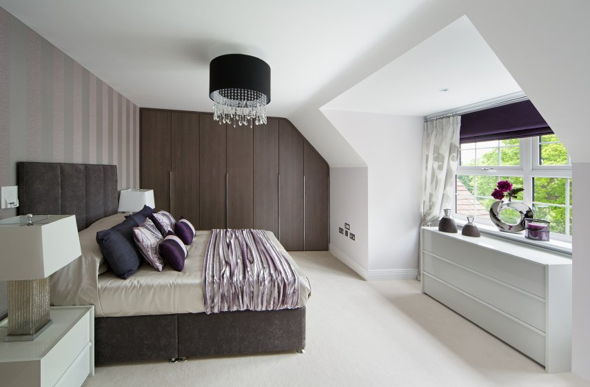 Primary bedroom featuring a gray-framed bed set on the white carpet flooring and is lighted by a stylish ceiling lighting.