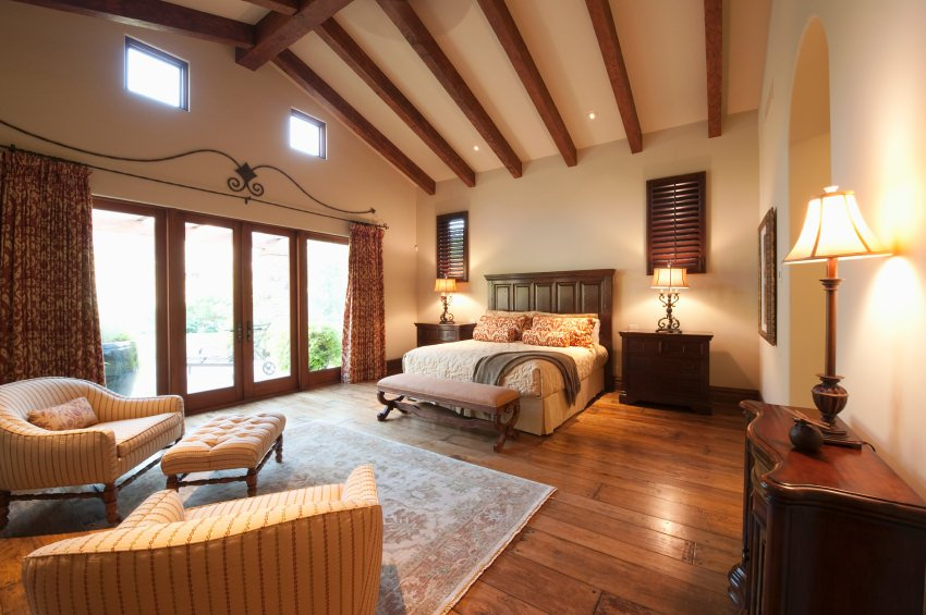 Cozy primary bedroom features a cathedral ceiling lined with exposed wood beams along with hardwood flooring. It has a sitting area with stripes armchairs and tufted bench.