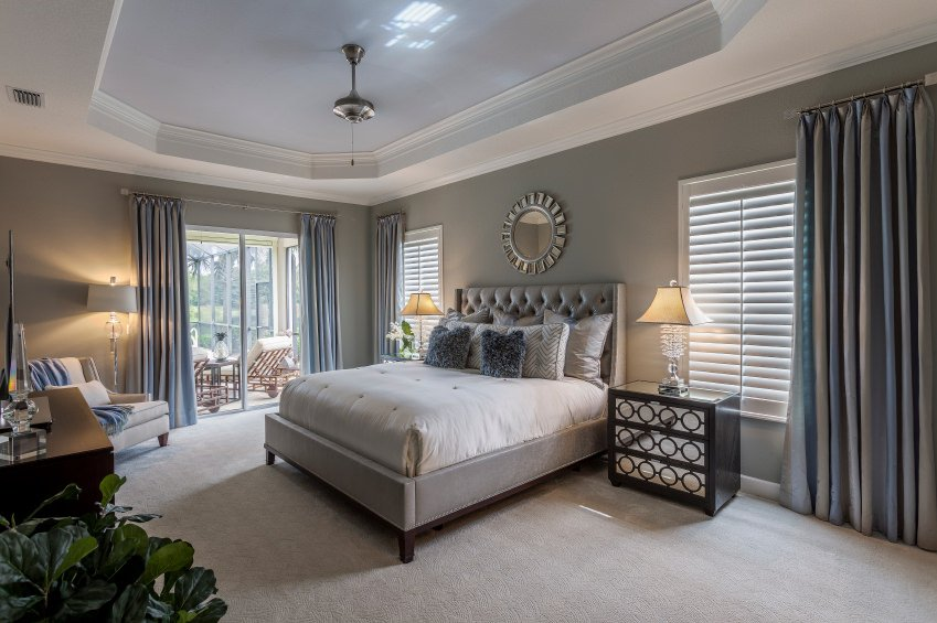 A master bedroom with a modish bed and a doorway leading to the patio area. The bedroom boasts carpet flooring, gray walls matching the gray window curtains and a tray ceiling.