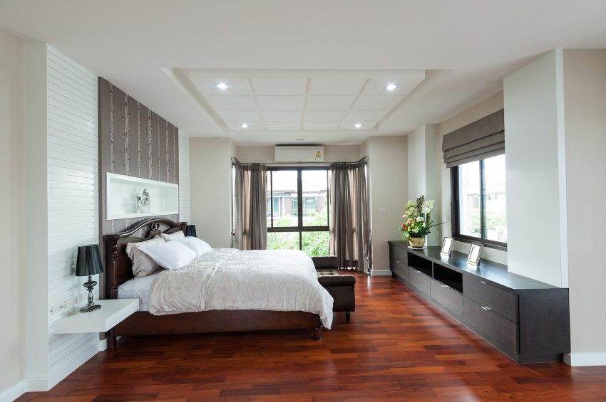 This primary bedroom features a classy bed set on the hardwood flooring. There's a very attractive ceiling as well.