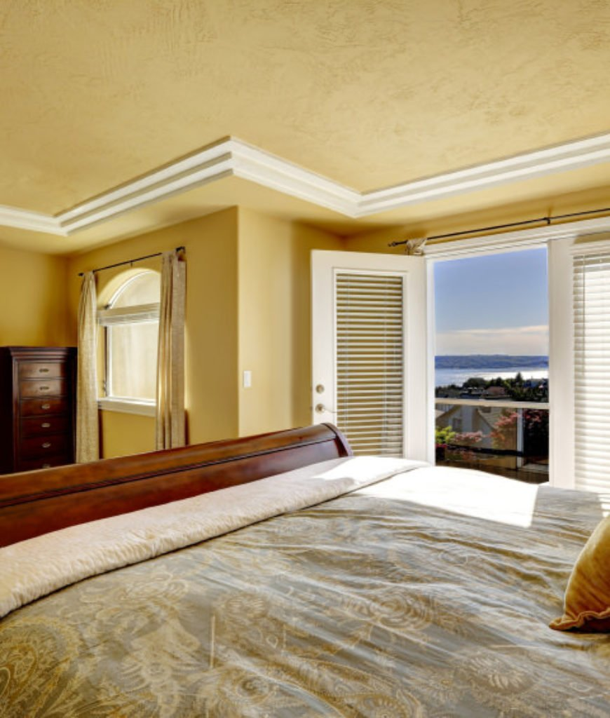 Luxury bedroom with walkout deck and fireplace