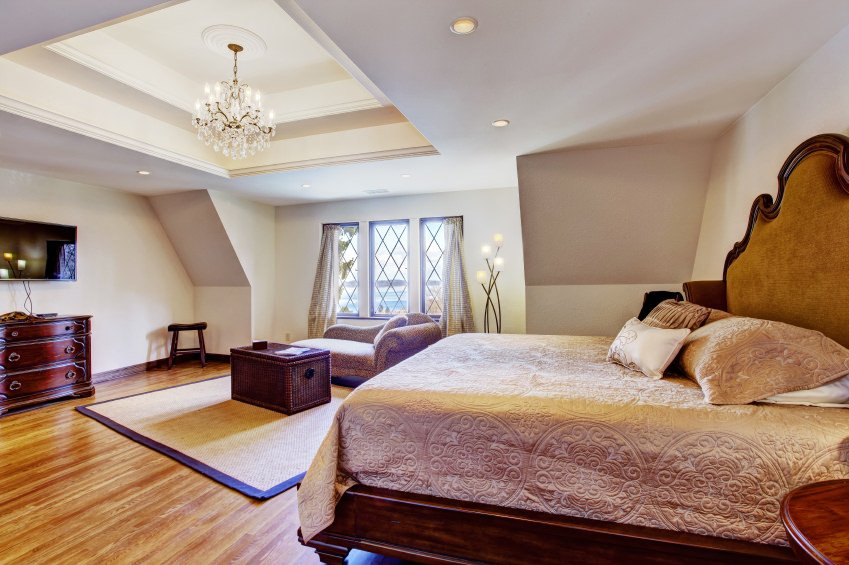 Primary bedroom featuring a luxurious bed along with an eye-catching tray ceiling lighted by a beautiful chandelier.