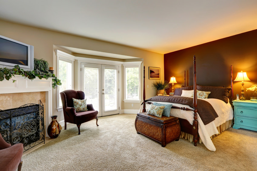 Luxury bedroom with fireplace. View of beautiful bed with high poles and antique chest
