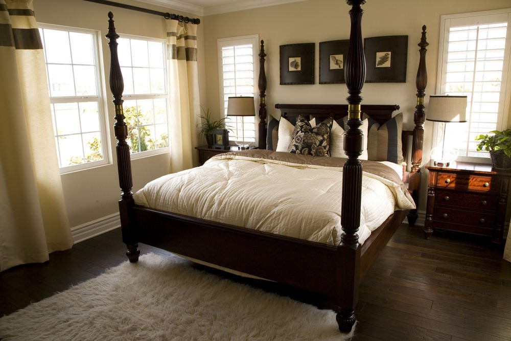A close up look at this primary bedroom's large bed set on the hardwood floors.