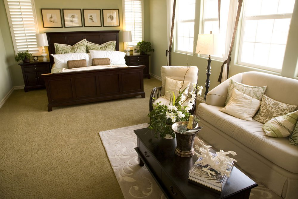 This master bedroom offers a large bed and a sitting area with a center table set on the rug on top of the carpet flooring. The room features green walls.