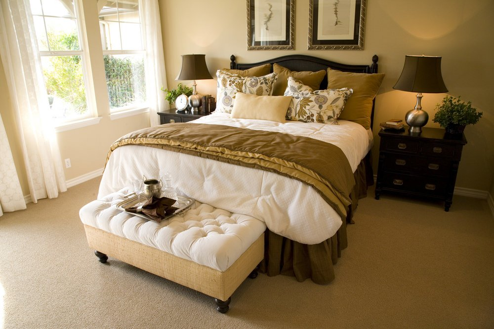 Master bedroom featuring a large bed with two side tables topped by a pair of table lamps. The room features carpet flooring and beige walls.