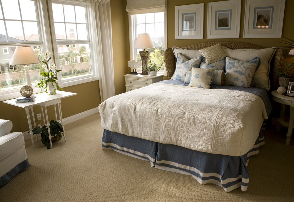 A master bedroom with a large bed set on the carpet flooring. The room features beige walls with white window curtains.