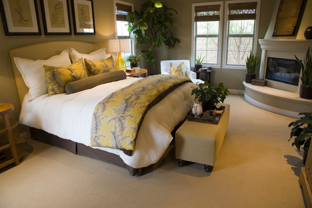 This master bedroom offers a large bed and a white chair on the side, along with a fireplace on the corner. The room features carpet flooring as well.