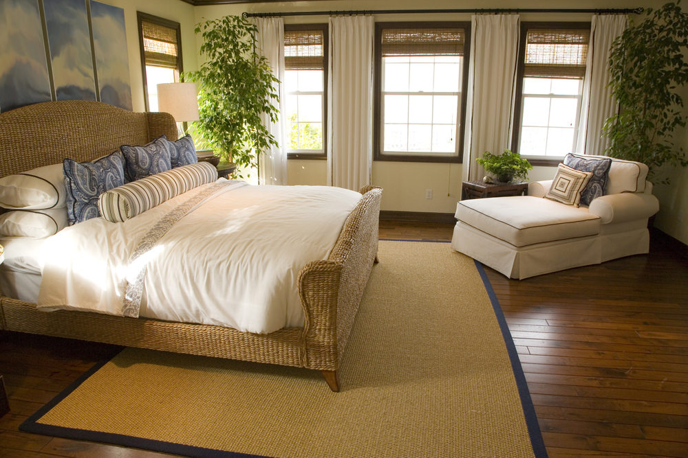 A primary bedroom with hardwood floors and a brown rug. The room also offers multiple indoor plants giving the room fresh air.