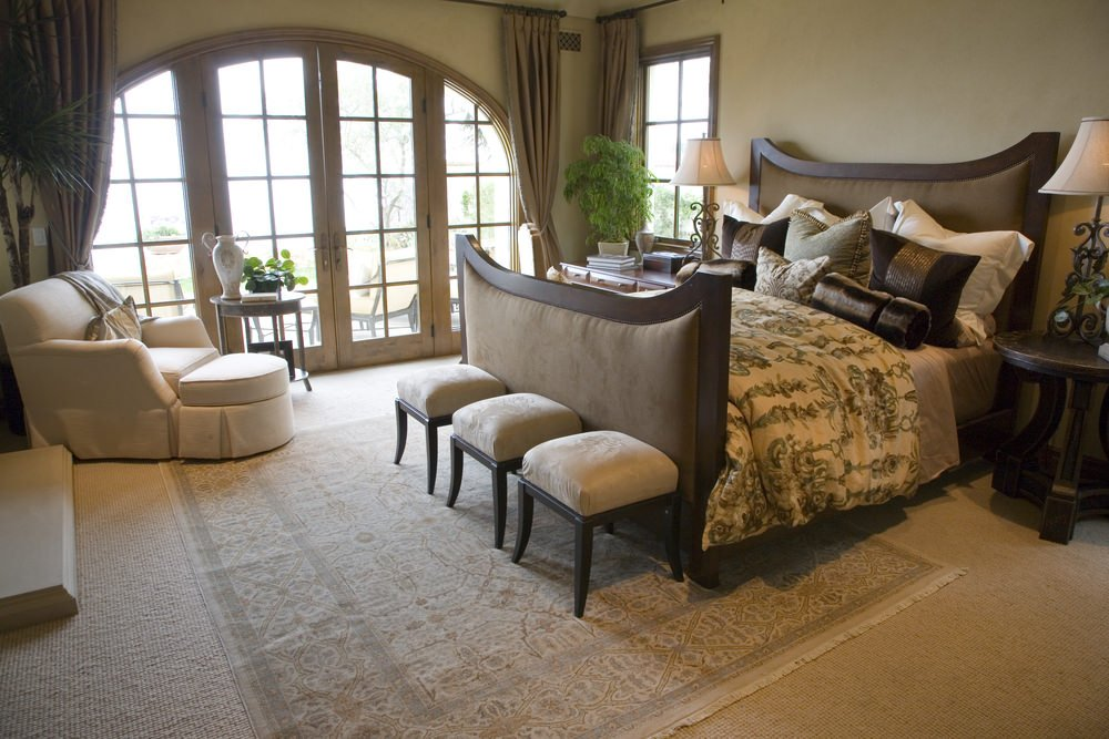 A primary bedroom featuring carpet floors topped by a classy rug. The room is surrounded by light brown walls.