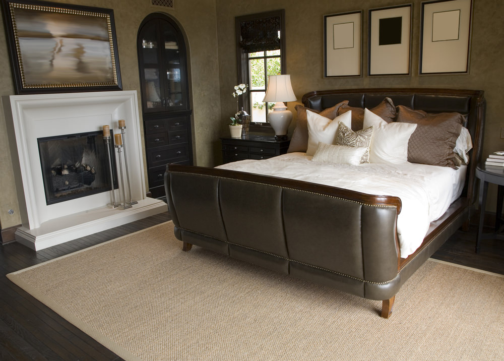 A close up look at this master bedroom's handsome looking bed and a white fireplace.