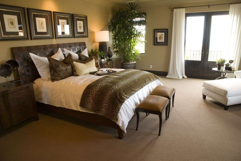 A master bedroom with a stylish bed set on the room's carpet floors. The room is surrounded by beige walls.