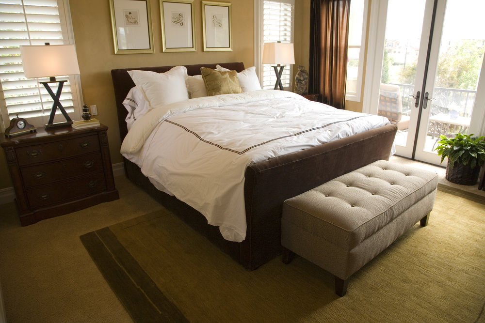 A focused shot at this master bedroom's large bed. The room features carpet flooring topped by a large rug.