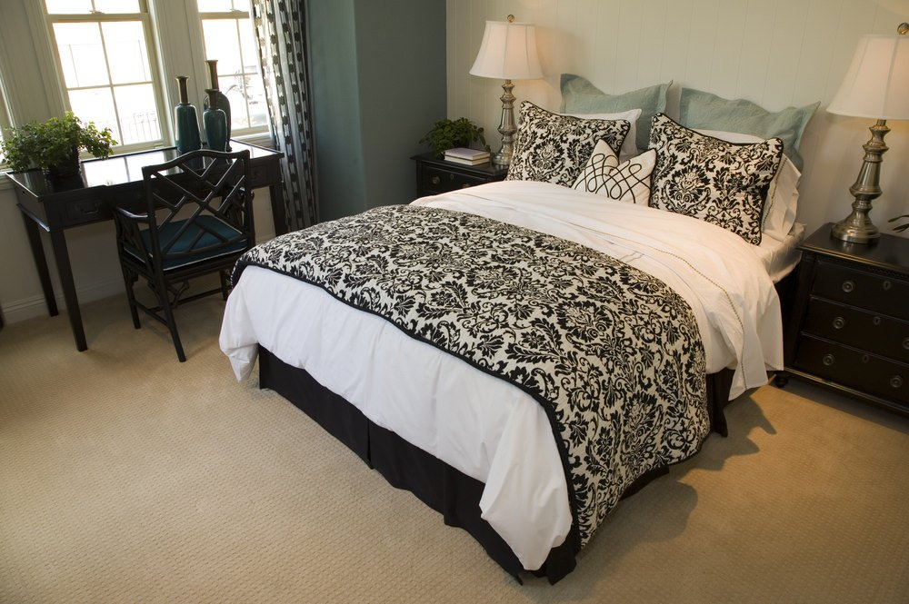 This bedroom offers a stylish bed and a black study desk near the windows. The room also features carpet flooring.