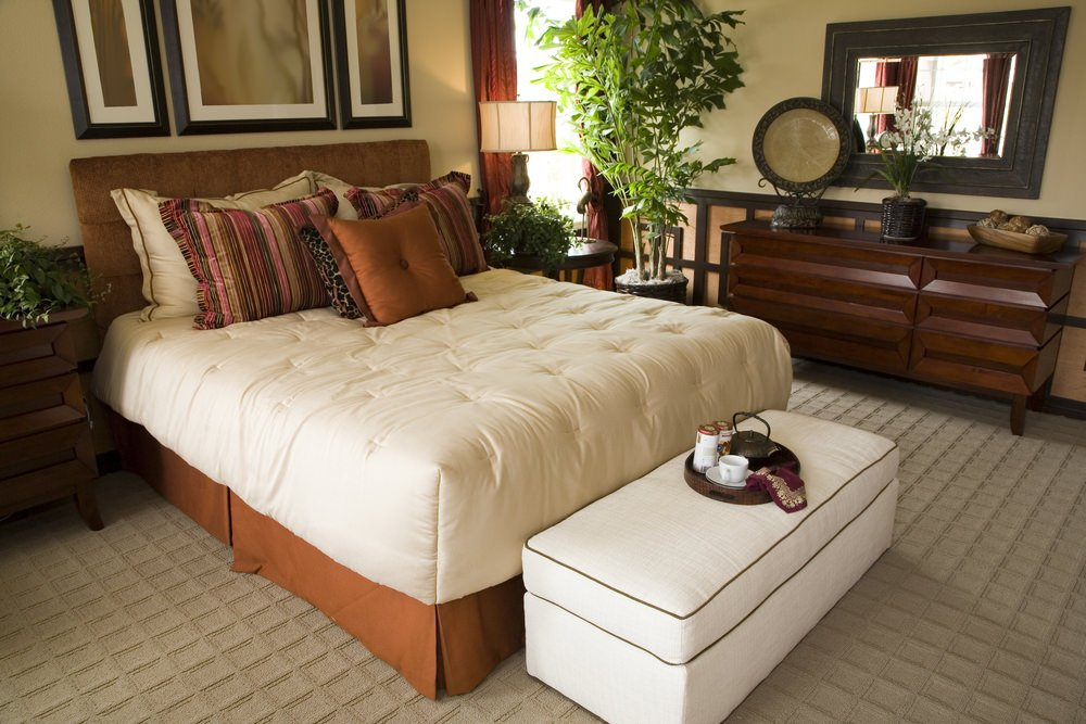A large bed set on this master bedroom's attractive carpet flooring. The room also features beige walls.