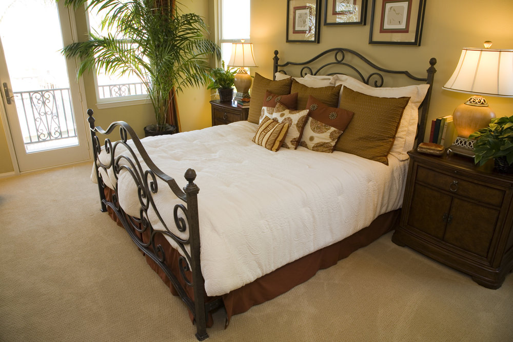 A close up look at this master bedroom's large bed. The room boasts carpet floors and beige walls, along with a doorway leading to a private terrace.