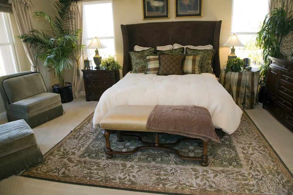 A master bedroom with a nice bed set on a handsome rug covering the carpet flooring. The room has multiple indoor plants for additional refreshing vibe.