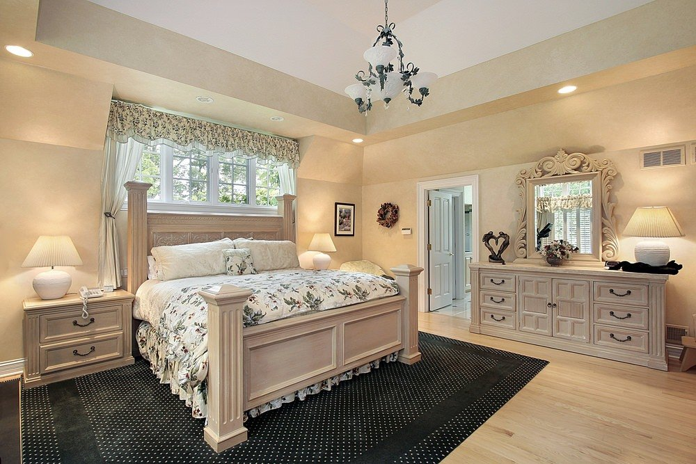 A chic primary bedroom with a stylish rug covering the hardwood floors, matching the beige walls.