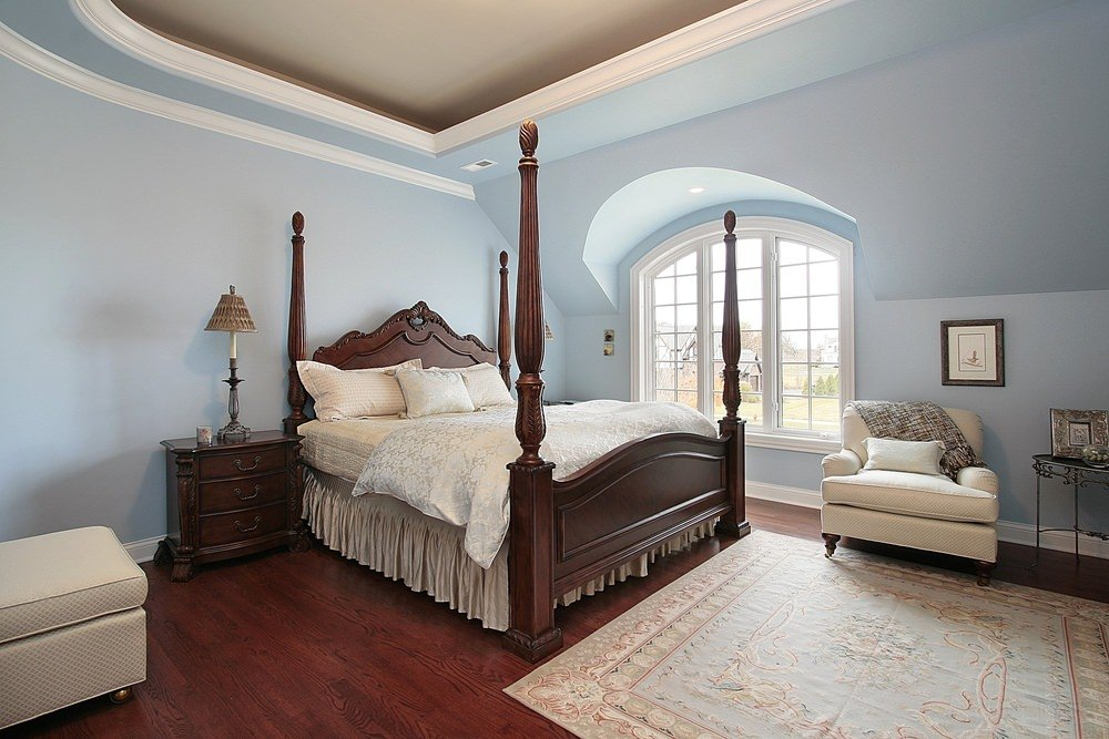 Large primary bedroom featuring light blue walls and a stunning ceiling, along with reddish hardwood flooring topped by a classy rug.