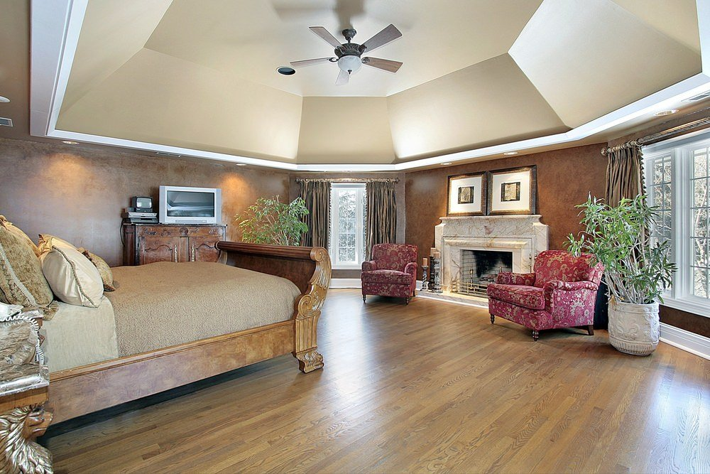 Large Modern Mediterranean primary bedroom boasting elegant walls and ceiling along with a hardwood flooring. The room offers a couple of elegant seats near the fireplace.