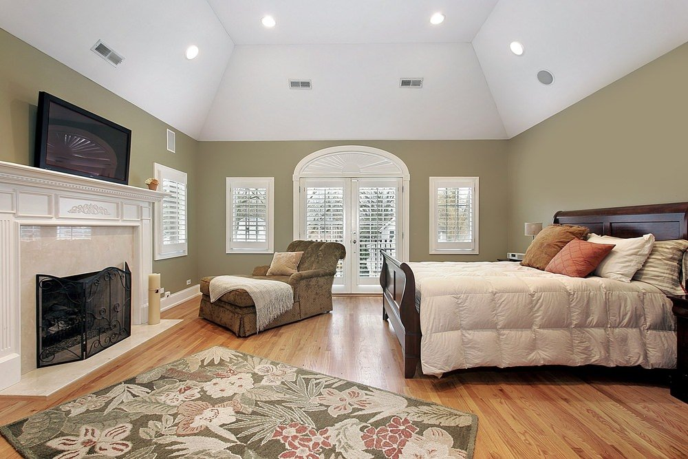 Large master bedroom featuring a hardwood flooring topped by a classy rug. There's a comfortable seat near the fireplace and a TV on wall.