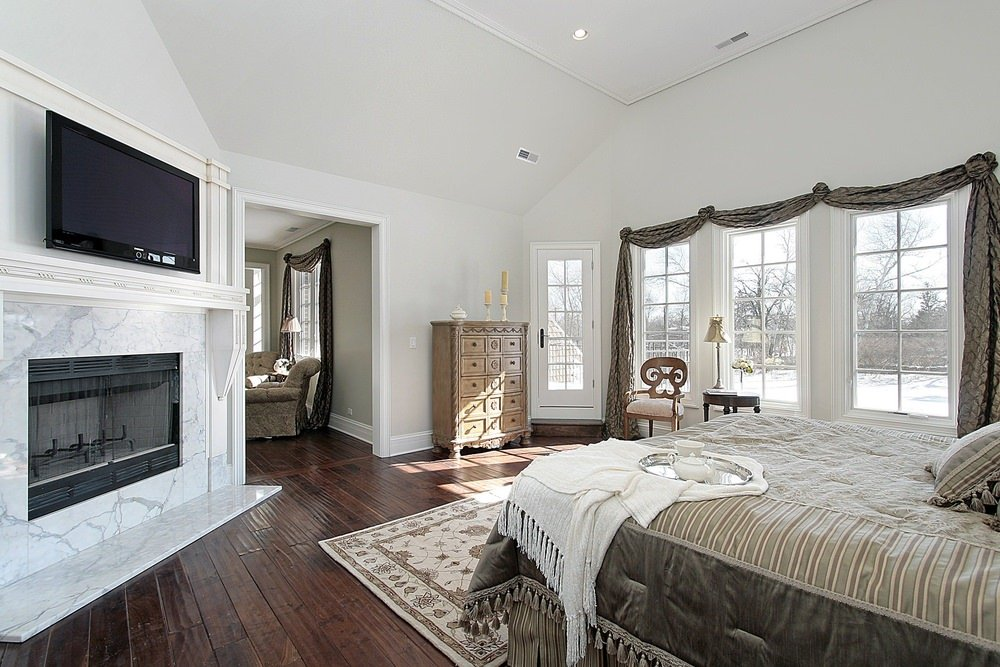 Large primary bedroom with its own living space. It also features a fireplace and a TV on top of it. It has light gray walls and hardwood flooring.