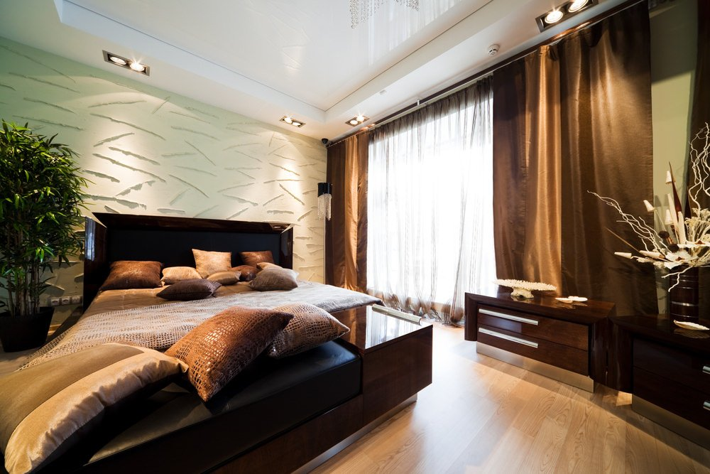 A luxurious primary bedroom featuring a large bed set on the hardwood flooring. The room features an attractive wall and elegant window curtains.