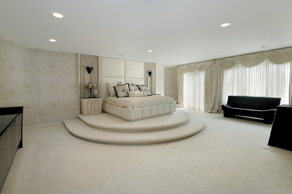 Huge master bedroom featuring white carpet flooring and luxurious-looking bed setup. There are black pieces of furniture as well to add color in the room.