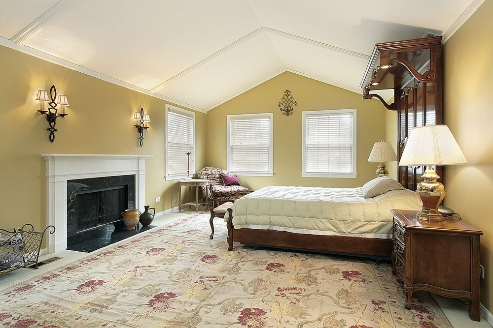 A classy master bedroom with a large rug, a fireplace and wall lights, along with a luxurious bed frame.