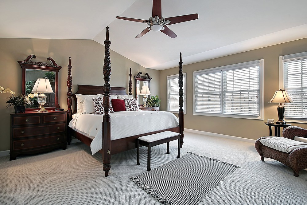 A traditional four poster bed sits on a carpet flooring in this beige master bedroom. It is in between redwood nightstands with mirrors and desk lamps.