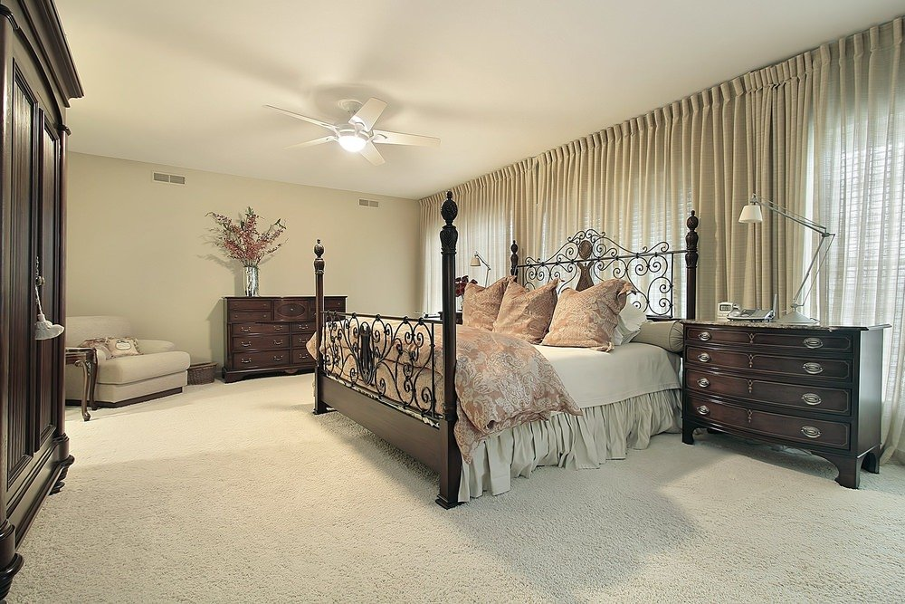 Master bedroom with an ornate bed frame and windows that run the length of the room covered in sheer curtains. It has dark wood nightstands that match the wardrobe and drawer cabinet.