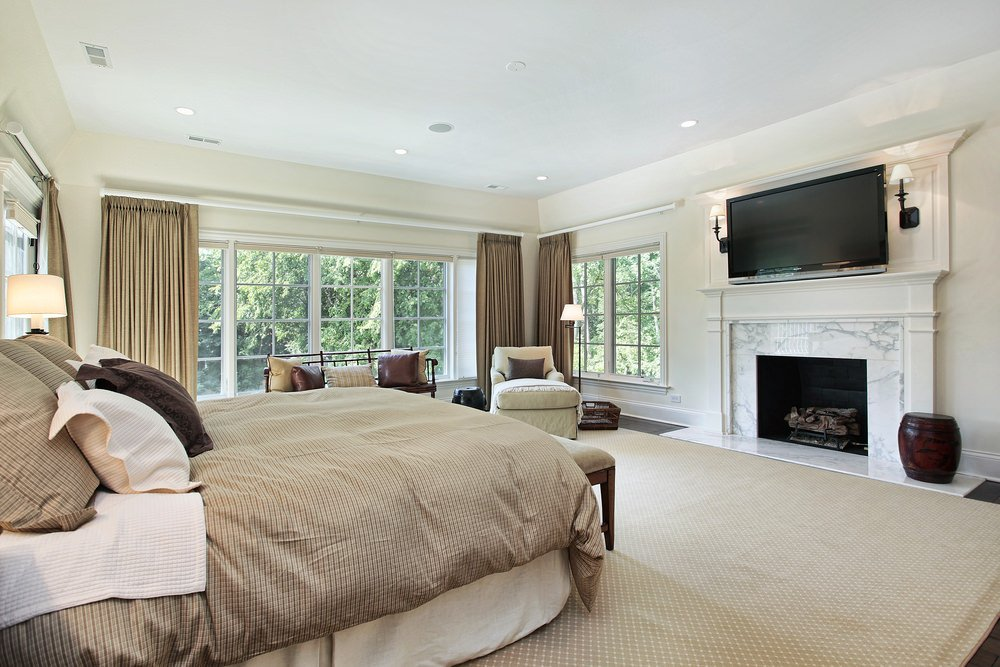 This primary bedroom offers a large bed, a sitting area near the windows, a fireplace and a widescreen TV on top of it, lighted by wall sconces.