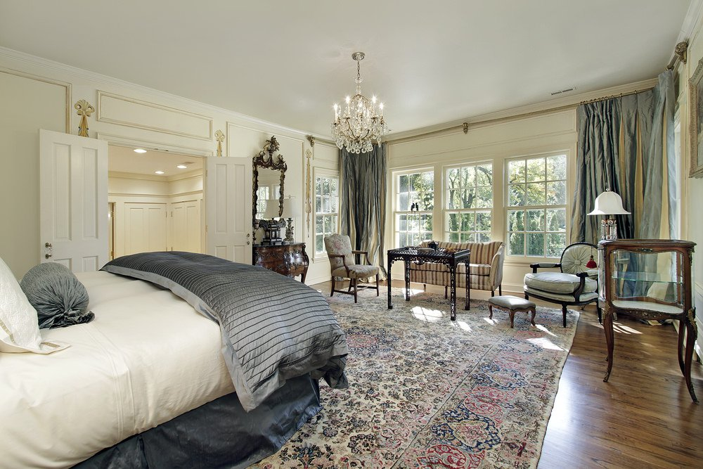 Large primary bedroom featuring hardwood flooring topped by a classy rug. The room is lighted by a gorgeous chandelier.