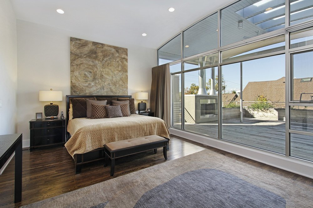 A modish primary bedroom featuring hardwood floors topped by a stylish rug. The room also features a high ceiling and a doorway leading to a private balcony deck.