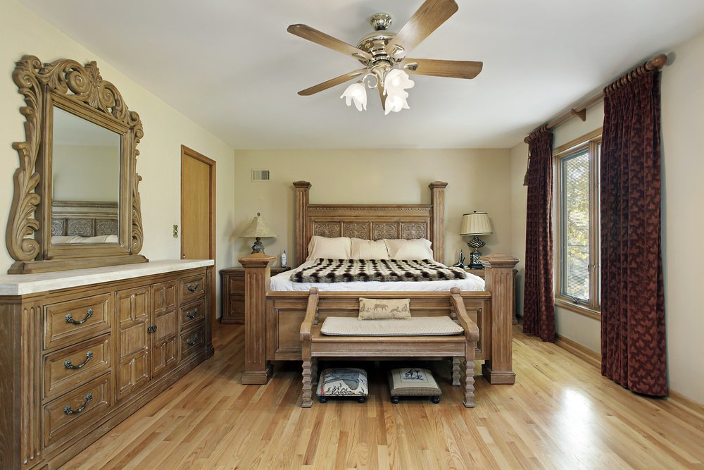 This primary bedroom offers a hardwood flooring matching the bed frame, cabinets and side tables.