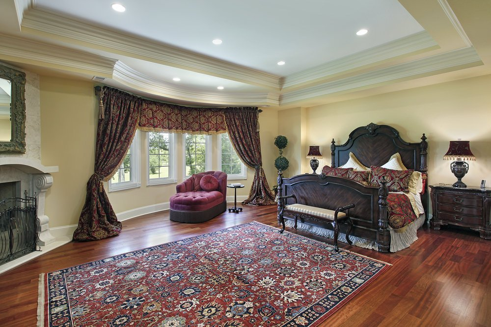 This primary bedroom offers an elegant looking bed and window curtains matching the beautiful rug covering the hardwood flooring. The ceiling looks so stunning as well.