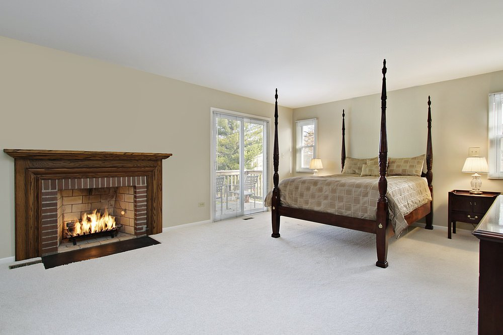 Simple primary bedroom boasts a four poster bed in dark wood and dressed in beige checkered bedding. It includes a fireplace with a wood mantel and brick firebox.