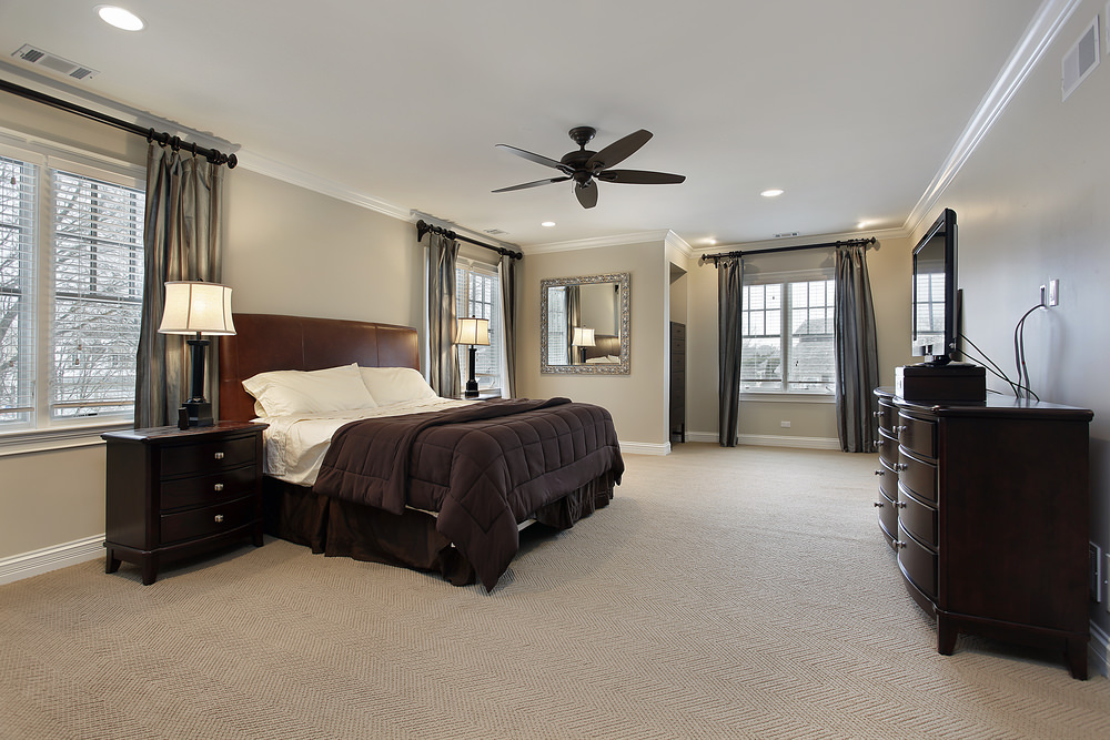 Spacious primary bedroom featuring light gray walls and carpet flooring, along with a regular ceiling lighted by recessed lights.