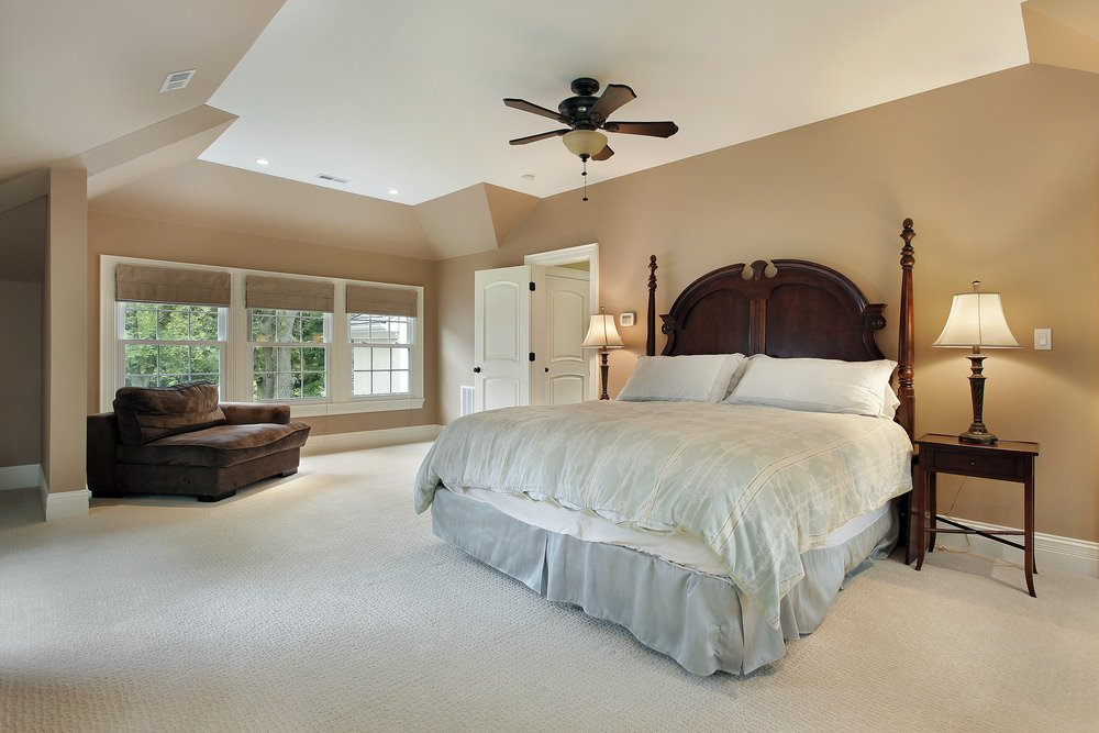 Primary bedroom features a wooden bed and nightstands with table lamps. It includes a brown velvet cuddle chair placed near the paneled windows.