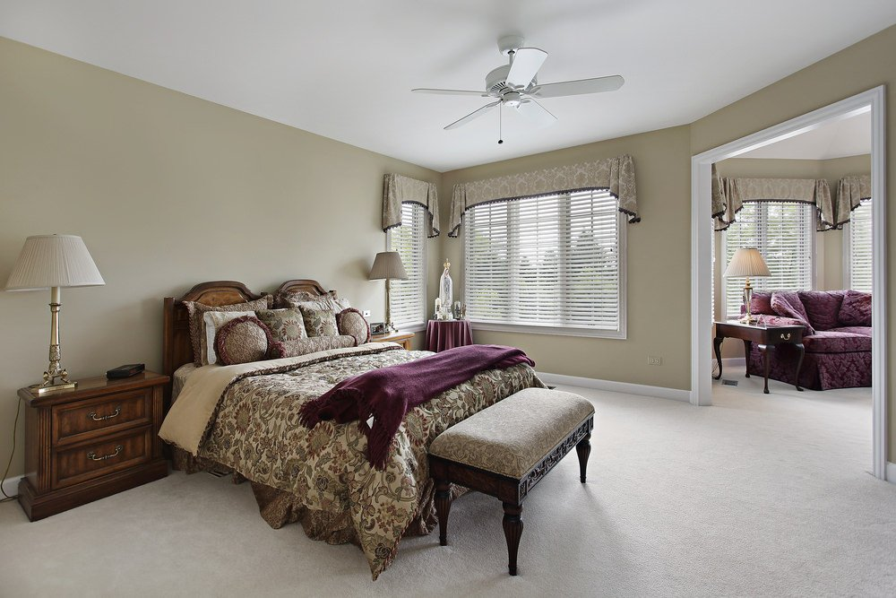 Beige primary bedroom with adjoining sitting area. It includes a wooden bed dressed in floral pattern bedding topped with a plum throw blanket that matches the sofa.