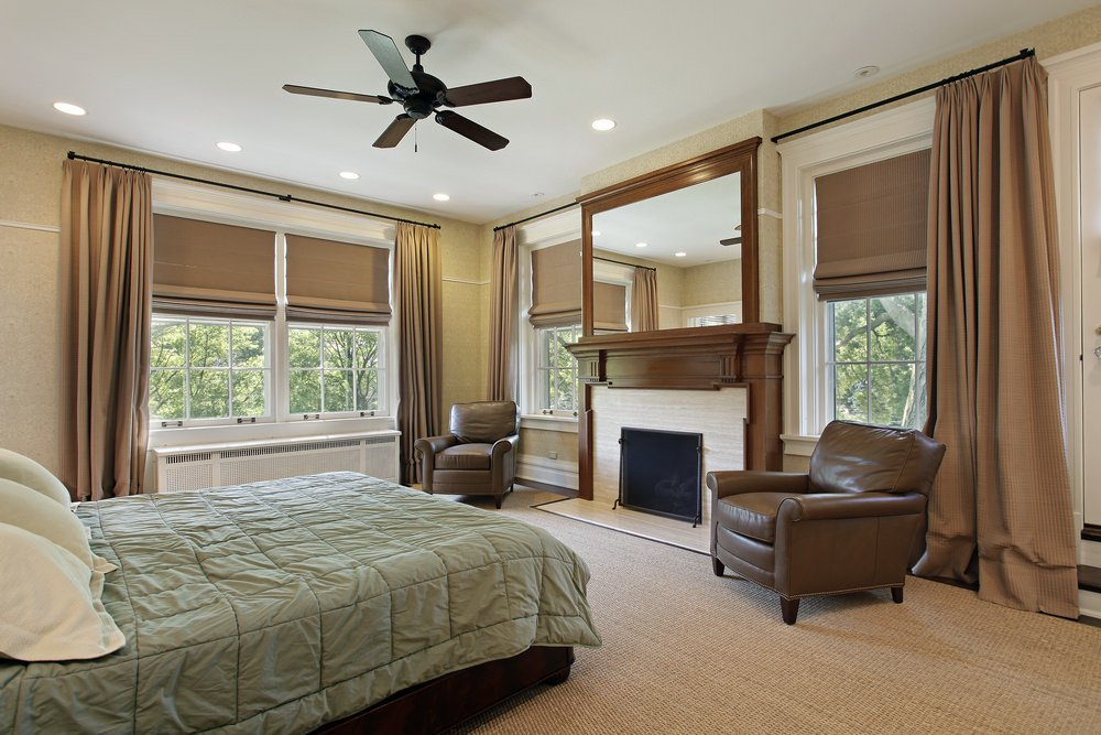 A classy primary bedroom featuring brown carpet flooring matching the brown window curtains and brown club chairs near the fireplace.