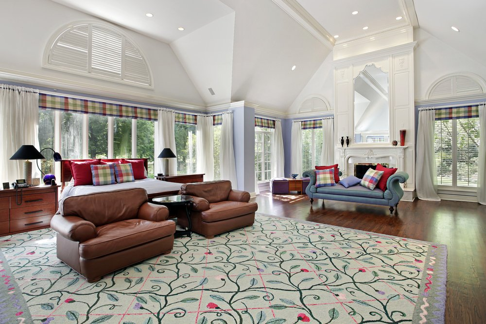 Large master bedroom featuring a hardwood flooring topped by a beautiful rug. There's a fireplace on the side as well.