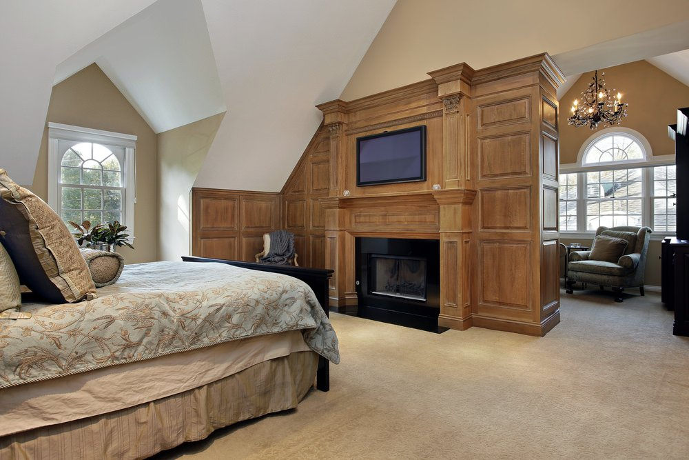 Classic primary bedroom boasts a flat panel TV and a fireplace fitted to the wooden wall separating the seating area that's lighted by a lovely candle chandelier.