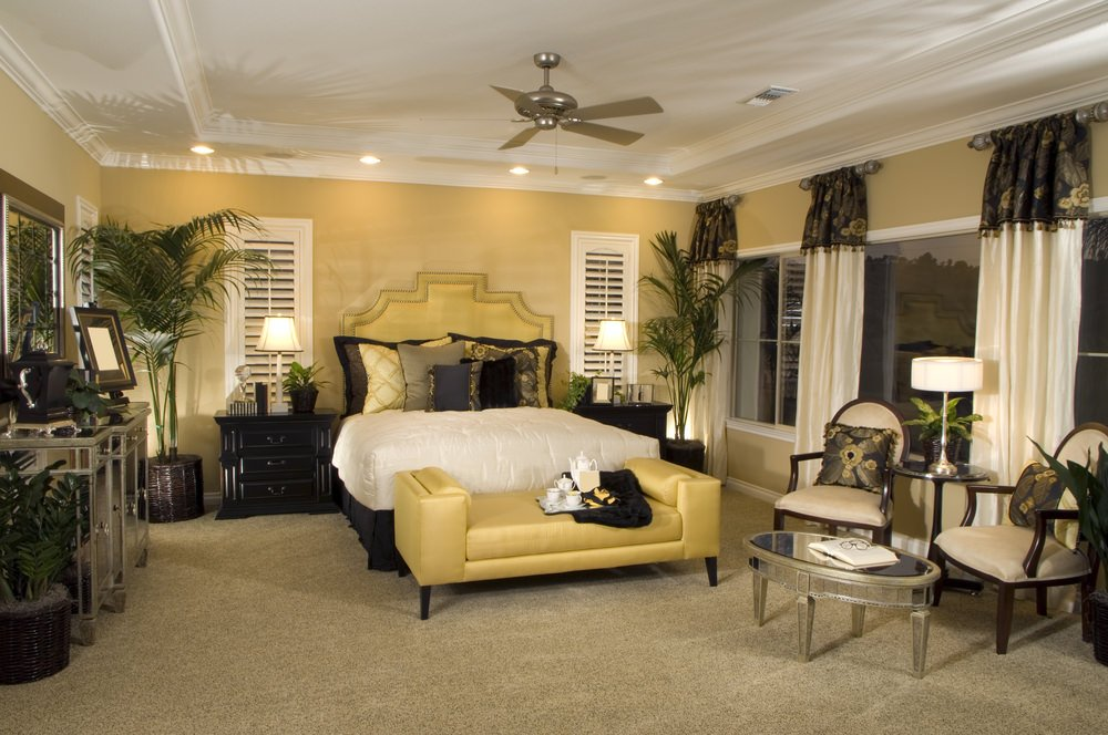 A classy master bedroom with a luxurious-looking bed along with a sitting area surrounded by beige walls and a tray ceiling.