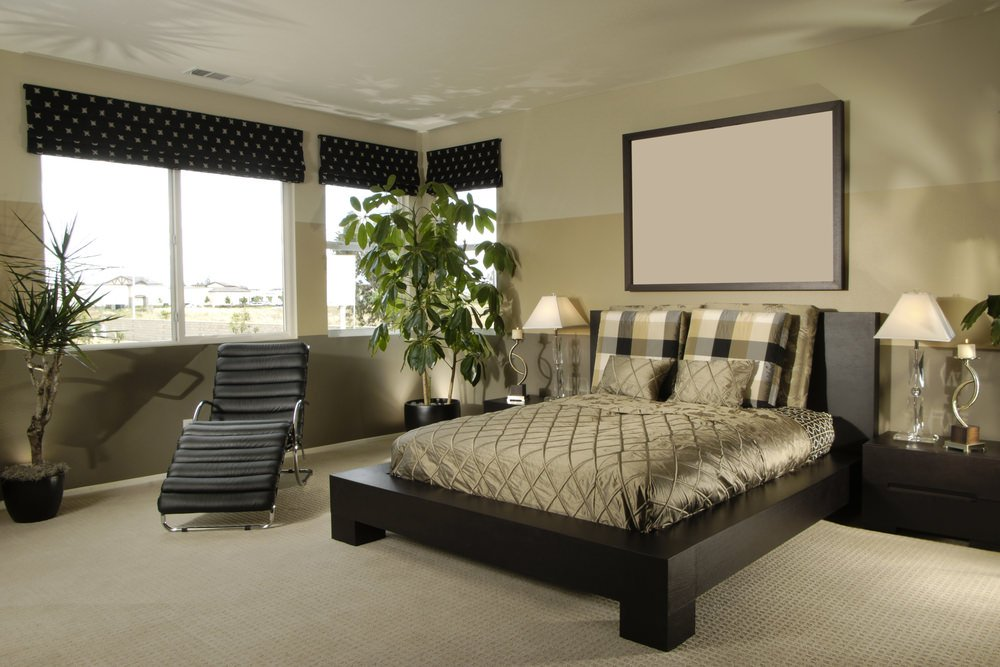 Modern master bedroom with a stylish bed set on the room's carpet flooring. The brown and beige walls look perfect together.