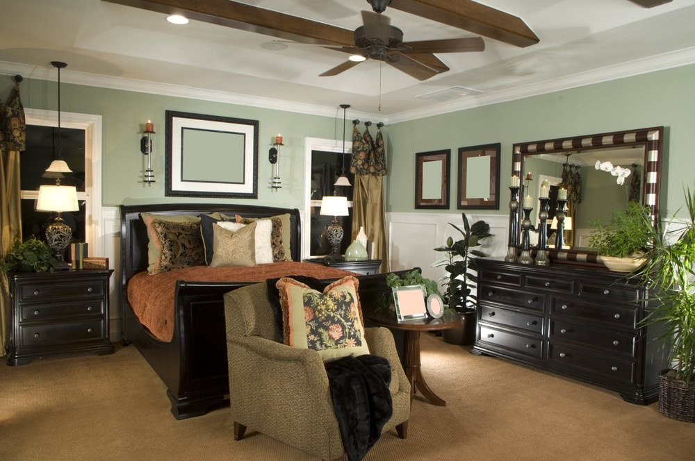 This master bedroom offers a stylish bed surrounded by green walls and a white tray ceiling, along with brown carpet flooring.