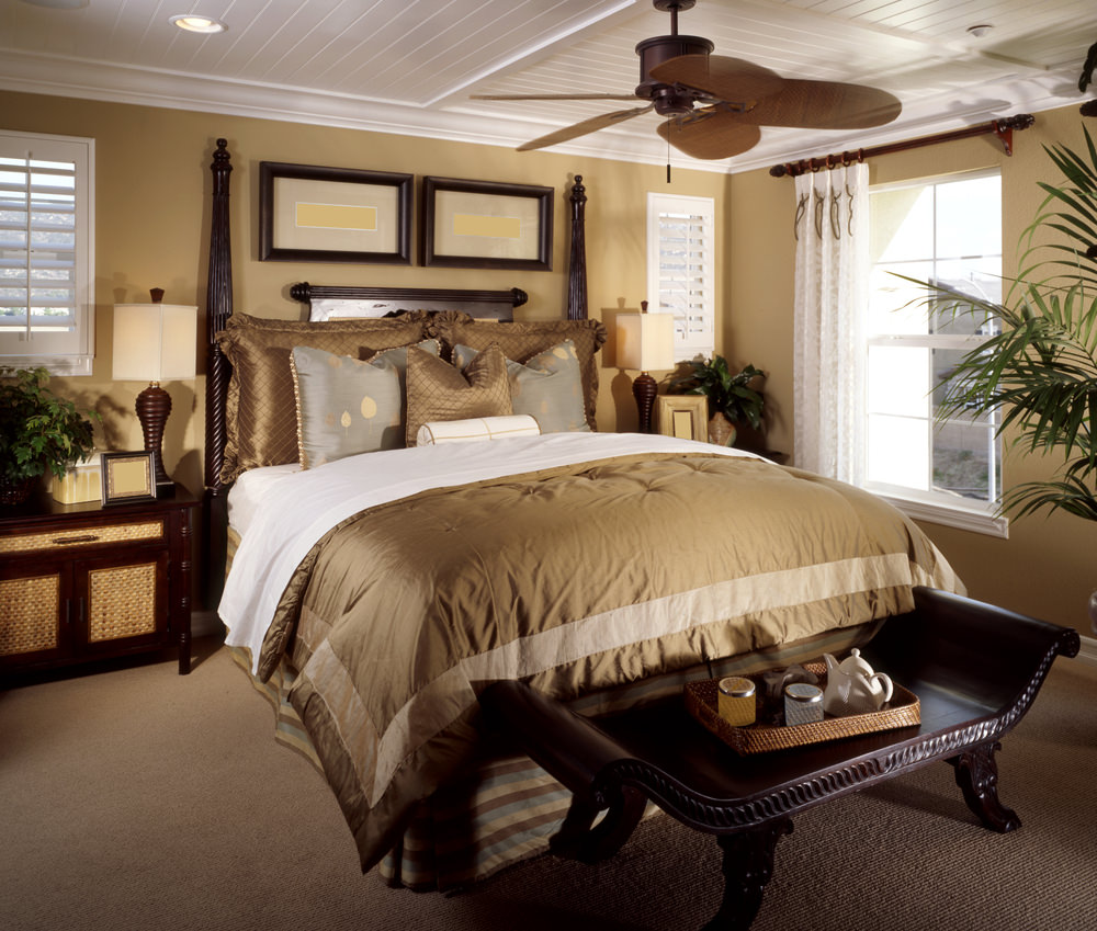 A close up look at this master bedroom's large bed with an elegant shade of gold. The room is surrounded by beige walls and has carpet flooring.