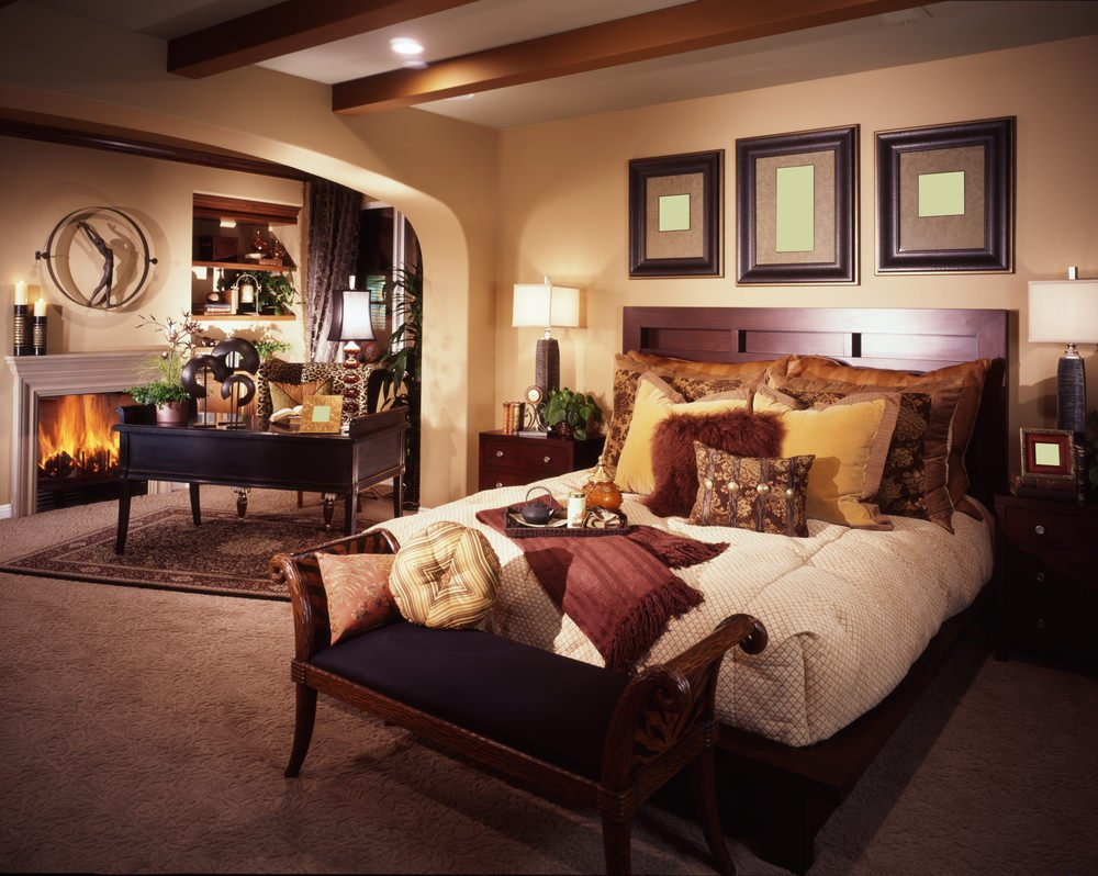 This master bedroom offers a comfy bed and a work desk near the fireplace. It has carpet floors topped by a classy rug.