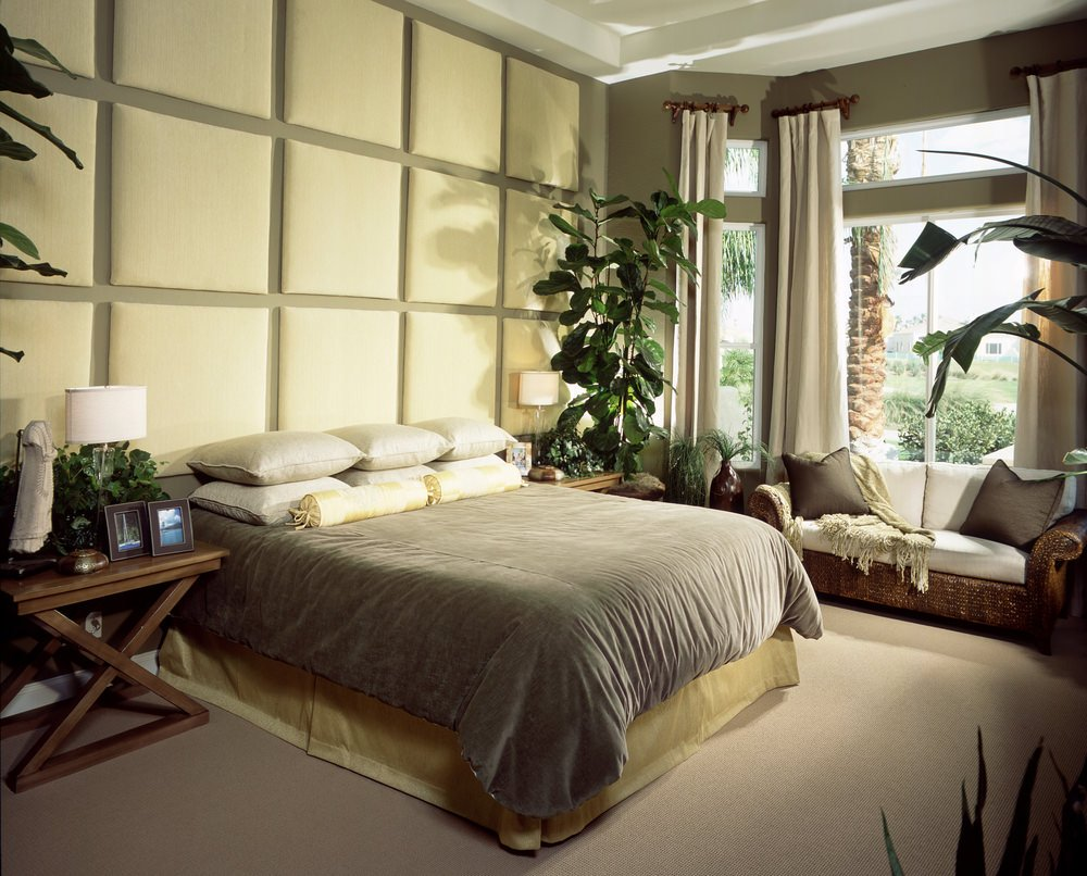 A classy master bedroom with a lovely wall and a large elegant bed, along with a sitting area near the window.